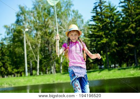 Cheerful girl with a butterfly net runs around the lawn on a sunny summer day.