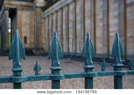 A vintage iron fence with greenish spearheads guards the approach to a historic stone building in Edinburgh Scotland.