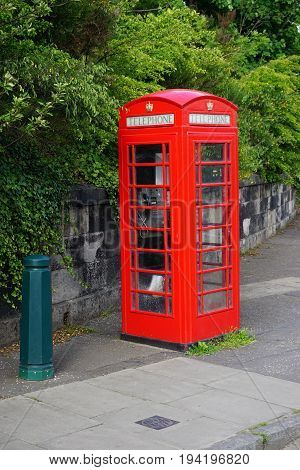 A classic vintage red British telephone booth on the sidewalk in Edinburgh Scotland. Many of these iconic phone booths have been retired from service and are being repurposed for other uses including sales kiosks and more.