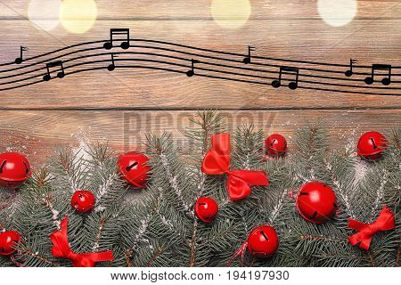 Composition with festive decorations and notes on wooden background. Concept of Christmas music and songs