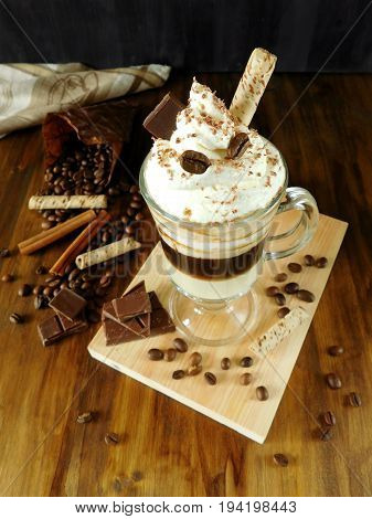 Coffee cocktail with whipped cream in an Irish coffee mug surrounded by coffee beans, cinnamon and chocolate bars