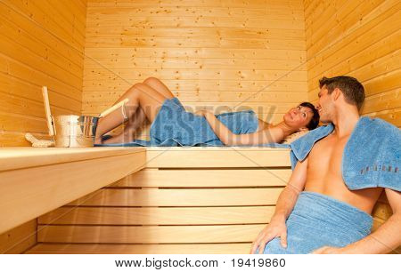 Young couple while beauty health spa treatment taking a sauna with towels and sweating