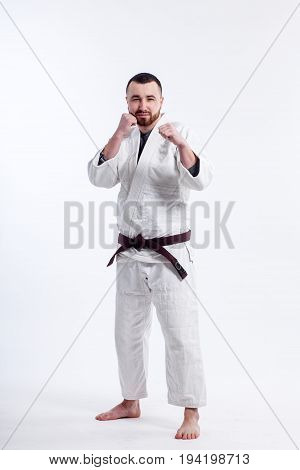 A young sporty man in a kimono. Jiu Jitsu Judo. Coach fighter Wrestler. White isolated background