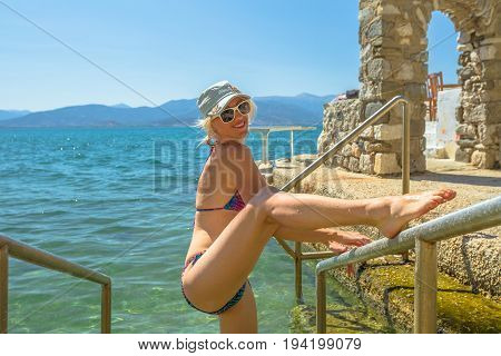 Summer. Happy tourist bikini vacation woman enjoying at semi-enclosed natural swimming pool, the Banieres, in Nafplio old town, Peloponnese, Greece, Europe. Happiness travel holidays lifestyle concept