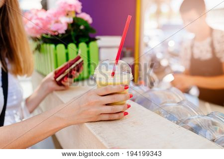 Woman buying banana smoothie in the roadside bar selling healthy snacks