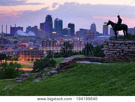 View of Kansas City Missouri skyline at dawn during golden light from the Kansas City Scout Memorial with all registered trademarks removed.