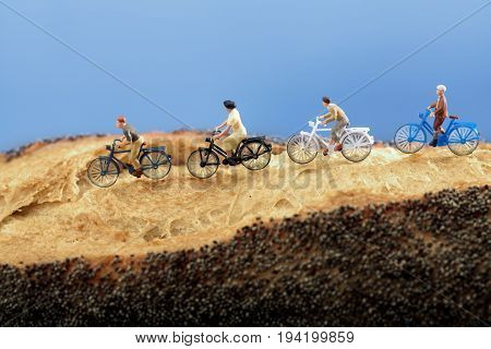 Miniature people: A group of cyclists enjoy rolling on a country road, with a blue sky on background