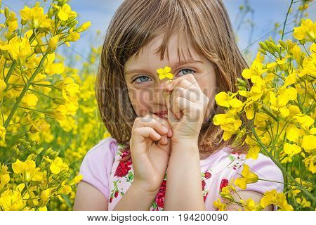 a happy little girl with colza flower