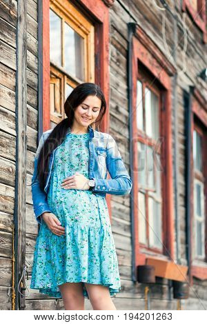 Young pregnant woman with a smile and hands on her stomach against the background of an old village house in a blue dress with a floral design and a denim jacket. Photo of a pregnant woman in summer