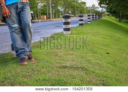 man leg standing beside the road with sunset light.