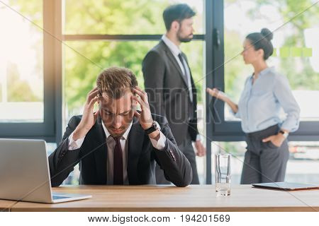 Overworked Businessman At Sitting Workplace In Office While Colleagues Having Discussion