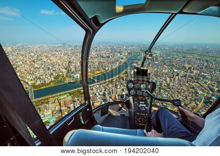 Helicopter cockpit inside the cabin flying on Tokyo city skyline, Sumida River Bridges and Asakusa area. Daytime. Tokyo, Japan.