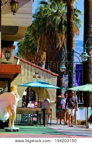 July 3, 2017 in Palm Springs, CA:  People walking beside retail shops and Palm Trees taken in Downtown Palm Springs, CA where tourists can experience shopping, dining, and entertainment in a relaxing desert ambiance