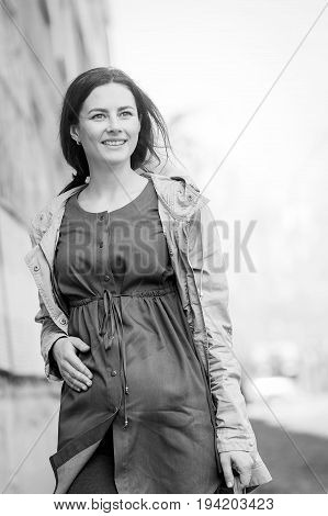 A black and white photo of a young fashionable pregnant woman with a smile and hands on her belly walks around the city in summer on a background. Photograph of a pregnant woman in summer