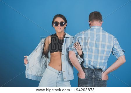 couple of stylish woman and man with back in sunglasses shirt and jeans jacket on blue background denim style beauty and fashion summer couple in love student lifestyle