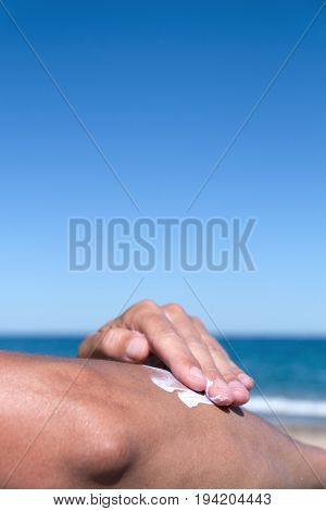 closeup of a young caucasian man on the beach man applying sunscreen to his arm, with a large blank space on top