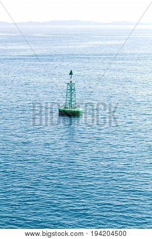 Green buoy floating in sea. Corfu island, Greece