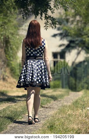 Young woman walking on village way. Woman in spotted dress and red hair. Sunny and positive rural scene with woman walking away from camera.