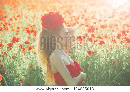 woman or happy smiling girl with long curly hair in red dress hold flower bouquet in field of poppy seed with green stem on natural background summer spring drug and love intoxication opium