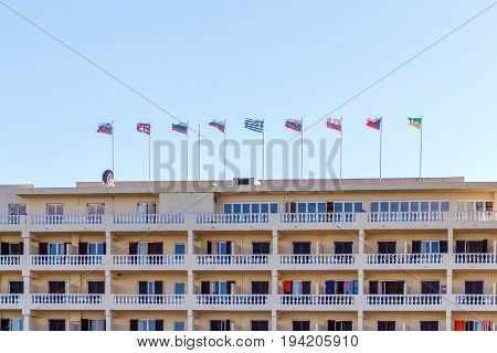 Different countries flags on hotel building. Corfu island, Greece. Daylight