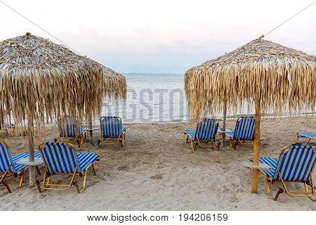 Corfu island beachside with chairs and umbrellas. Greece, sunset view