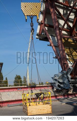 Crane's cradle (working platform cherry picker or basket) in the construction site.