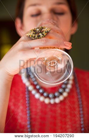 Beautiful woman in the red blouse drinking champagne. Close-up.