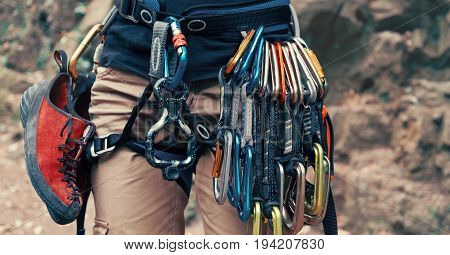 Unrecognizable climber young woman wearing in safety harness with climbing equipment outdoor