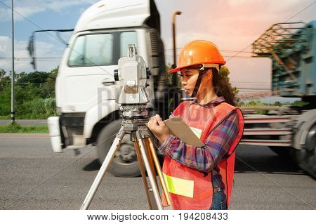 Female surveyor or Engineer making measure by Theodolite with partner on the highway.
