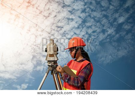 Female surveyor or Engineer making measure by Theodolite with partner on the field and blue sky background.