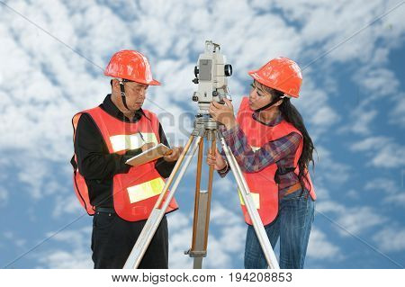 Surveyor or Engineer making measure by Theodolite with partner on the field and blue sky background.