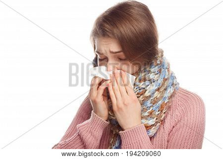 Young woman feeling ill and blowing her nose isolated on white.