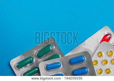 Colored Pills, Tablets And Capsules On A Blue Background. Medicine And Health.