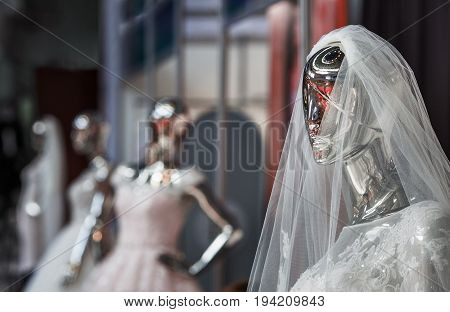 The dummy looking as liquid terminator in a wedding attire of the bride shining the polished metal.