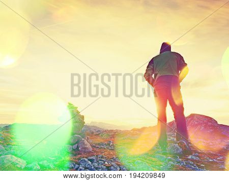 Film Grain Effect.   Tourist Guide At Stocked Stones On Alps Peak. Strong Hiker Enjoy Sunset