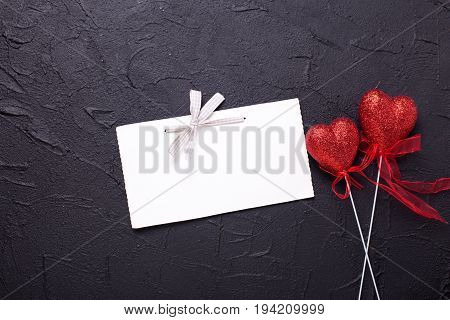 Empty tag and two red hearts on textured black background. Place for text. Flat lay.