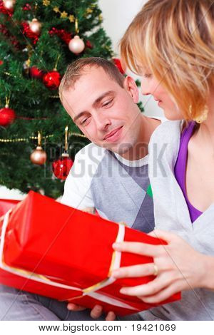 Happy smiling lovely couple celebrating christmas eve with present gifts