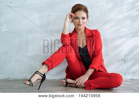 Beautiful brown haired woman in nice red pantsuit sitting on floor and posing at camera studio portrait