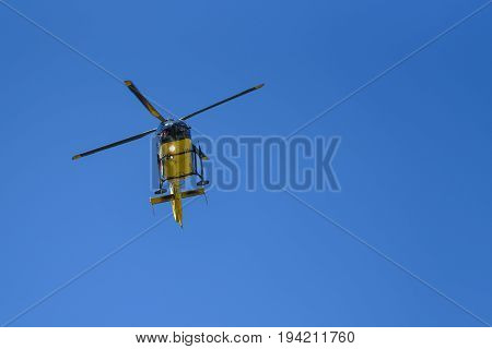 Generic yellow helicopter used for firefighting and rescue operations on the blue sky background - low angel view.