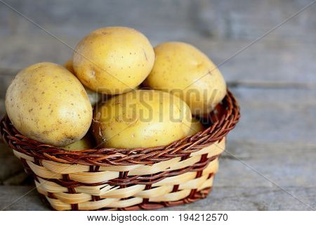 New potatoes. Whole new potato in a wicker basket on a vintage wooden background. Closeup