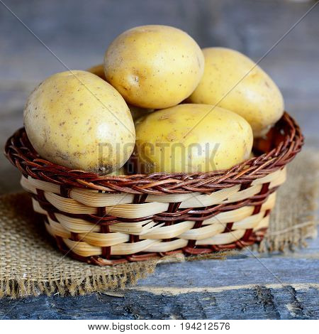Young potatoes. Whole young potato in a wicker basket on a vintage wooden table. Closeup