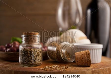 Close up of spices in mason jars with olives in plate on table