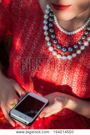 Woman in the red blouse holding smartphone.
