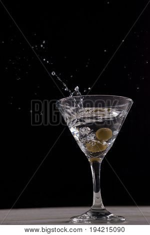 Vodka splashing in martini glass with olives against black background