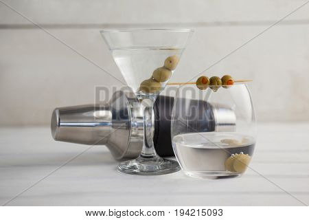Green olives in vodka martini with cocktail shaker on wooden table