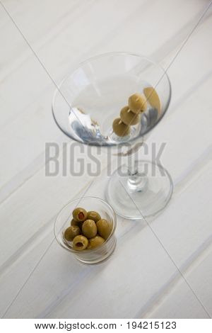 High angle view of olives in container by vodka martini on table