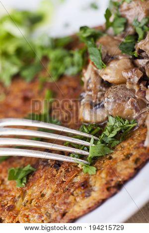 potatoe pancakes with mushroom sauce with a fork