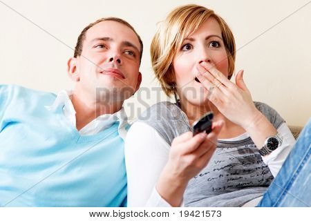 Lovely weekend couple sitting on couch watching tv while woman is shocked