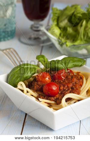 portion of spaghetti bolognese with salad with wine