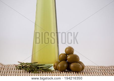 Green olives and rosemary by oil in bottle on place mat